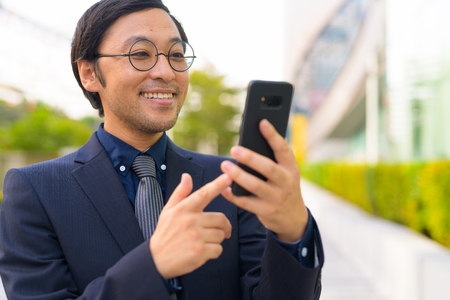 Face of happy Asian businessman using phone in the city outdoors