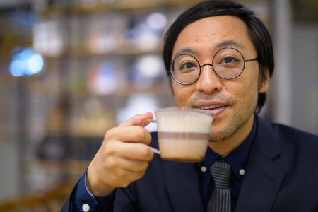 Face of happy Asian businessman drinking coffee 写真素材 - 118448780