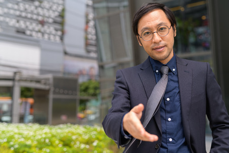 Asian businessman giving handshake outside the office building 写真素材 - 118448833