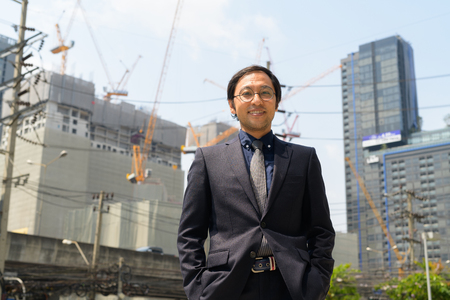 Happy Asian businessman smiling against view of construction site Stock Photo