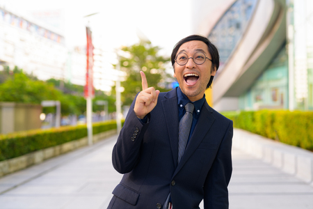Happy Asian businessman thinking while pointing finger up outdoors Stockfoto