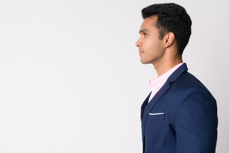 Profile view of young handsome Indian businessman in suit