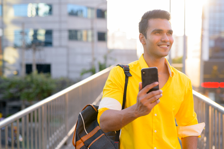 Happy young Indian man with backpack thinking while using phone on the footbridge Reklamní fotografie