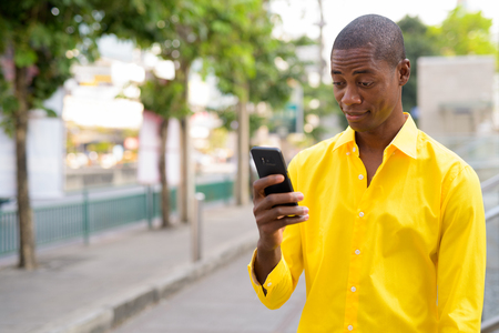 Young bald African businessman using phone in the city streets outdoors