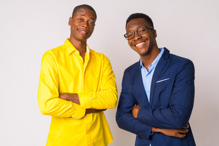 Two young happy African businessmen smiling with arms crossed together