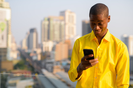 Happy young bald African businessman using phone against view of the city
