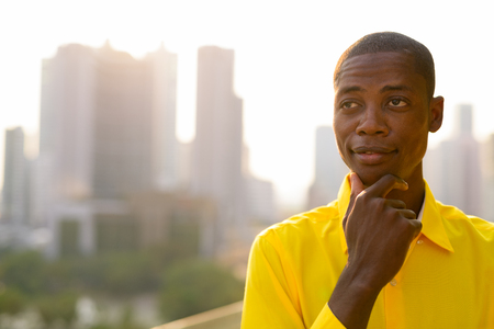 Young bald African businessman thinking and looking up against view of the city