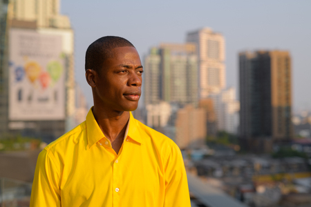 Young thoughtful bald African businessman against view of the city Foto de archivo
