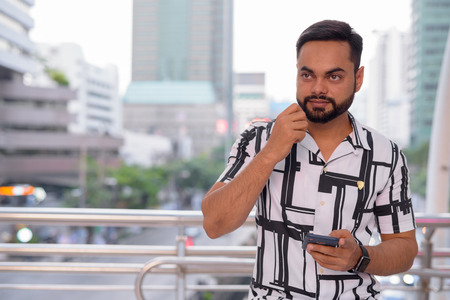 Young bearded Indian man thinking and using phone against view of the city streets