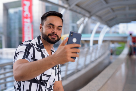 Young bearded Indian man taking selfie on the footbridge outdoors