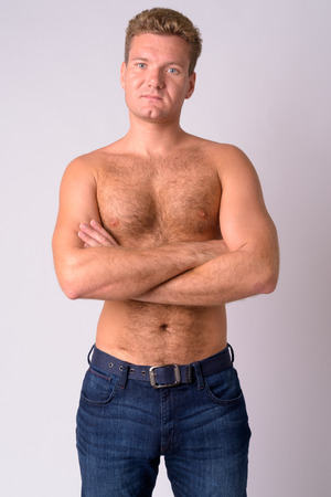 Portrait of young blonde shirtless man with chest hair crossing arms