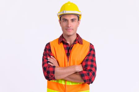 Jonge knappe Spaanse man bouwvakker met gekruiste armen Stockfoto