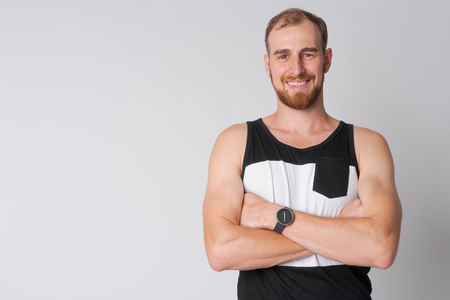 Portrait of happy young bearded man smiling with arms crossed Imagens
