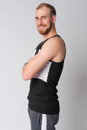 Profile view of happy young bearded man smiling with arms crossed