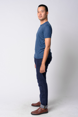 Full body shot profile view of young Asian man looking at camera