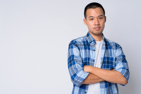Portrait of young Asian hipster man with arms crossed
