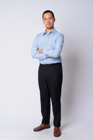 Full body shot of young Asian businessman with arms crossed