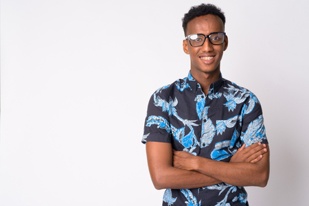 Young happy African tourist man with eyeglasses smiling and crossing arms