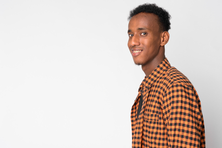 Profile view of young happy African hipster man looking at camera