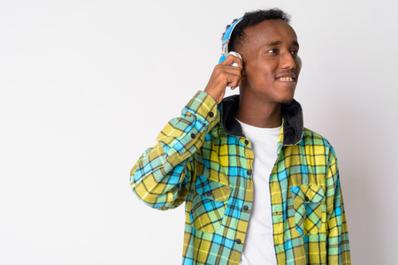 Portrait of young happy African hipster man listening to music and thinking