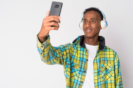 Portrait of young happy African hipster man listening to music and taking selfie