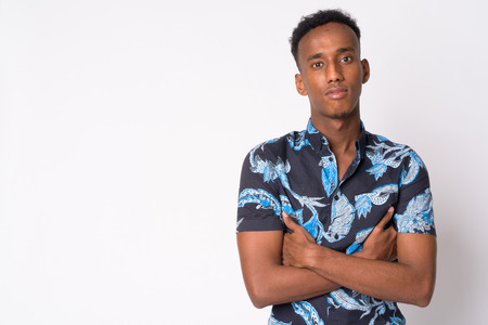 Portrait of young handsome African tourist man with arms crossed