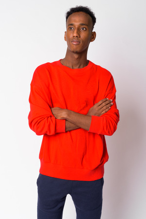 Portrait of young handsome African man thinking with arms crossed