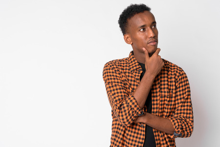 Portrait of young handsome African hipster man thinking and looking up Stock Photo
