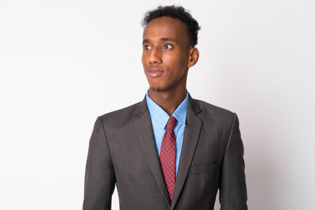 Portrait of young handsome African businessman in suit thinking