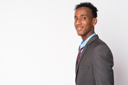 Profile view of young happy African businessman looking at camera Stock Photo