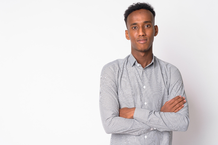 Portrait of young handsome African businessman with arms crossed