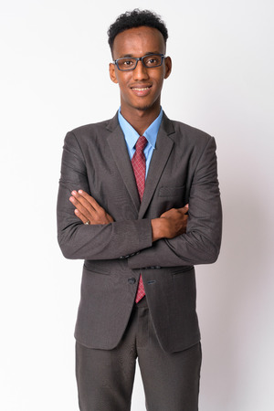 Portrait of young happy African businessman with eyeglasses crossing arms Banco de Imagens