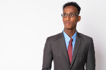 Portrait of young handsome African businessman with eyeglasses thinking