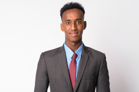 Studio shot of young handsome African businessman with Afro hair wearing suit against white background