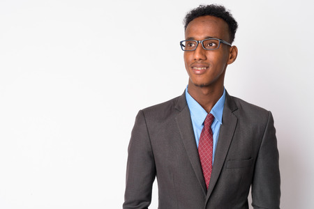 Portrait of young happy African businessman with eyeglasses thinking