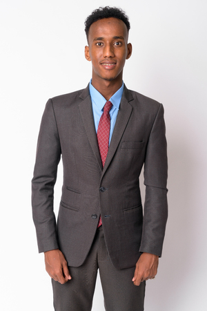 Portrait of young happy African businessman in suit smiling