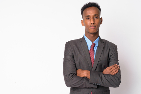 Portrait of young handsome African businessman in suit with arms crossed Stock Photo