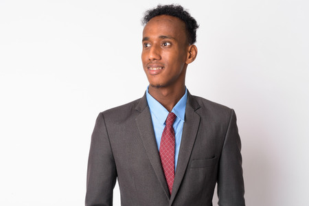Portrait of young happy African businessman in suit thinking Stock Photo