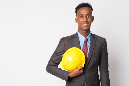 Portrait of young happy African businessman with hardhat