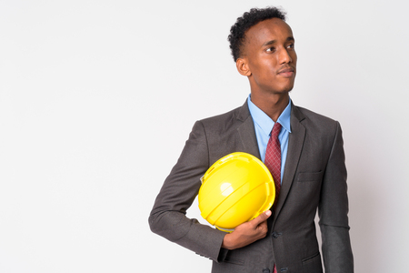Portrait of young handsome African businessman with hardhat thinking