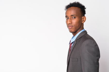 Profile view of young handsome African businessman looking at camera