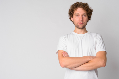 Portrait of handsome man with curly hair crossing arms