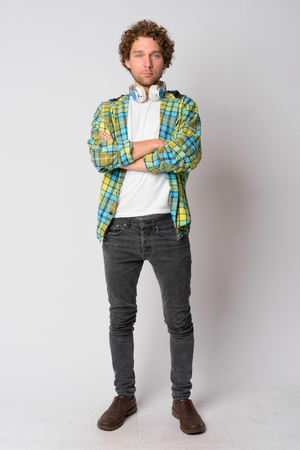 Full body shot of handsome hipster man with curly hair crossing arms