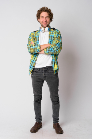 Full body shot of happy hipster man smiling and crossing arms