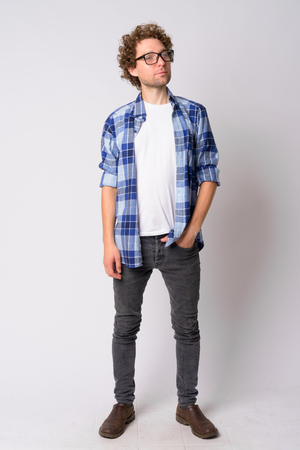 Full body shot of handsome hipster man with eyeglasses thinking