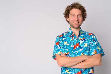Happy handsome tourist man with curly hair smiling and crossing arms