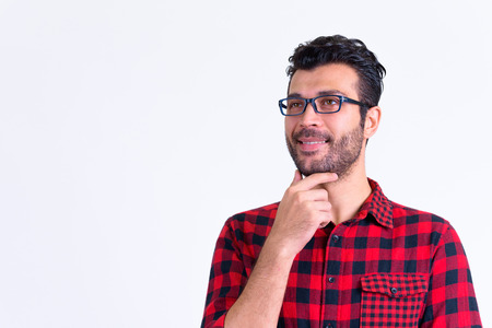 Portrait of happy bearded Persian hipster man thinking