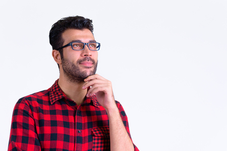 Portrait of handsome bearded Persian hipster man thinking