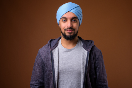 Young bearded Indian Sikh man wearing turban against brown backg