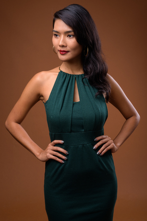 Studio shot of beautiful Asian businesswoman against brown backg Stock Photo